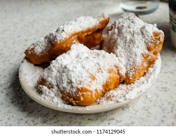 Fresh beignets come out of the fryer, topped with powdered sugar, ready to eat.