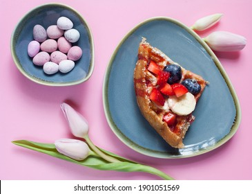 Fresh Belgian Waffle with starwberry, banana, blueberry and fruit syrup and Easter sweets -  sugar coated eggs.