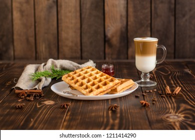 fresh belgian waffles, tasty jam and latte coffee on a wooden background. top view.