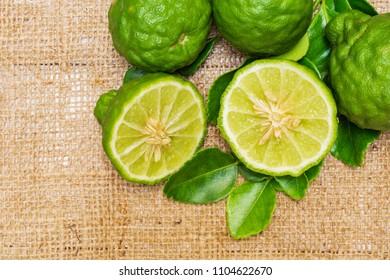 Fresh bergamot fruit,  bergamot slice and bergamot leaves on cloth sack background;