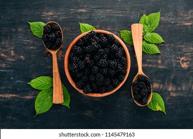 Fresh berries blackberries. On a black wooden background. Top view. Free space for text.