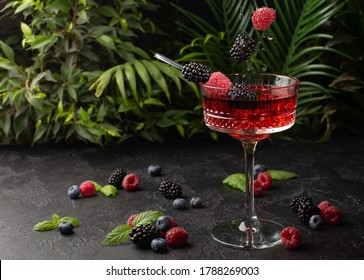 Fresh berries cocktail with raspberry,blackberry,mint and ice with tropical plants on background.Shot of drink in freeze motion,flying drops and berries.Summer cold drink and cocktail.