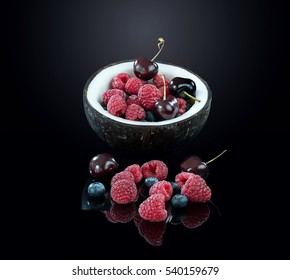 Fresh berries in the coconut on black background