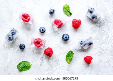 fresh berries with mint in ice cubes on stone background top view