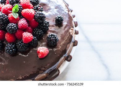 Fresh berries and mint leaf on chocolate cake on marble table, selective focus, copy space
