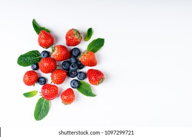 Fresh berries on white background, top view. Strawberry, blueberry and mint leaf, flat lay
