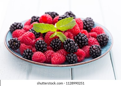Fresh berries in a plate on a  wooden background. Flat lay, top view, copy space.