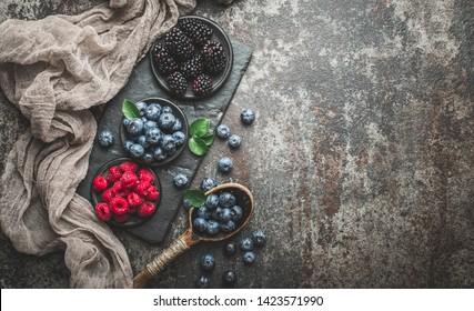 Fresh berries with raspberries, blueberries, blackberries in bowl on a stone stand on a dark metal background.