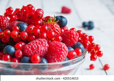 Fresh berries (raspberry, red currant, blueberry) in glass bowl on wooden table