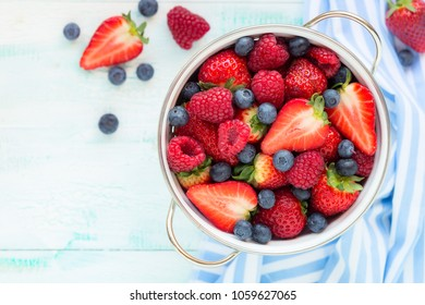 Fresh berries - strawberries, raspberries and blueberries - in a while colander. Overhead view with copy space for your text, recipe or greeting