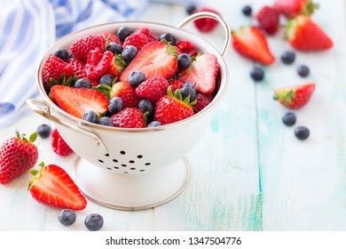 Fresh berries - strawberries, raspberries and blueberries - in a while colander on white wooden background with copy space