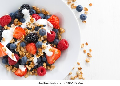 fresh berries, yogurt and homemade granola for breakfast, close-up, top view, horizontal