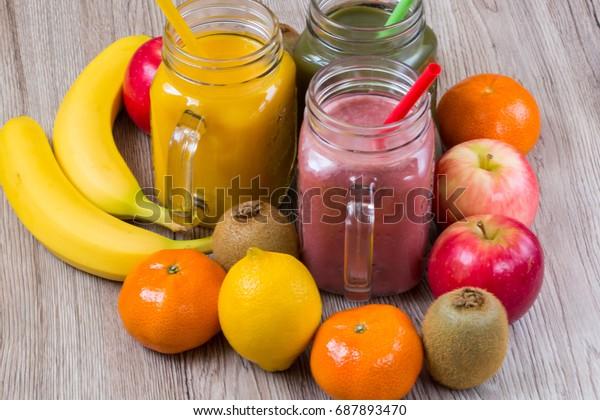 Fresh berry and fruits smoothie, healthy juicy vitamin drink diet or vegan food concept, fresh vitamins. Apples, kiwi, bananas, strawberries, lemon.