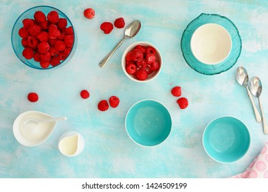 Fresh from the berry patch ripe red raspberries with aqua and white dishes on rustic wooden background.  Shot from overhead in flat lay composition.