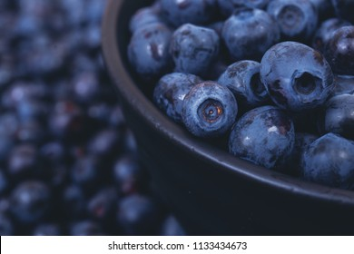 A lot of fresh bilberries in black bowl on bilberries background. Close-up. Macro.