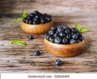fresh bilberries or blueberries in small wooden bowls on a rustic table, selective focus