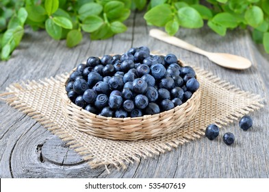 Fresh bilberry in a wicker basket on wooden table, close up