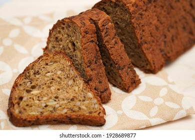 Fresh black bread with sunflower seeds cut into pieces on a wooden background. Selective focus.