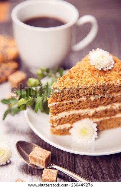 fresh black coffee in white cup with cake on wooden background