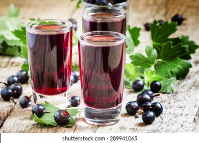 Fresh black currant juice with berries in glasses on an old wooden table, selective focus