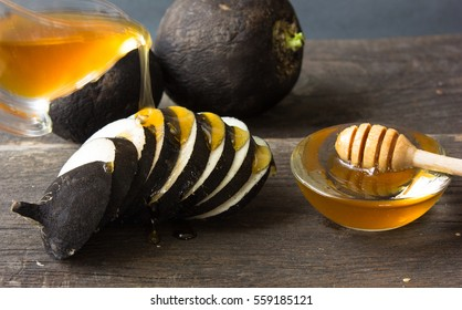Fresh black radish roots  with honey on wooden background.