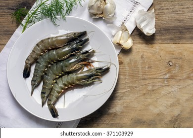 fresh black tiger shrimps on a white plate ready for preparation on a rustic wooden board, garlic and dill garnish, view from above, copy space