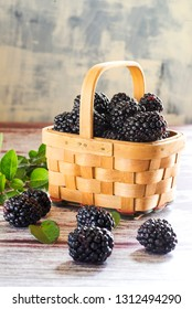 fresh blackberries close-up in a wicker basket on a textured table