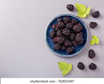 Fresh blackberries on a plate with blackberry leaves, on gray background, top view, copy space.