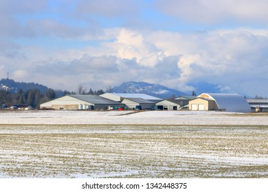 A fresh blanket of snow during the early Spring covers a wide open acreage in a rural valley.