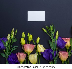 fresh blooming flowers Eustoma Lisianthus and empty paper card on black  background, top view, copy space