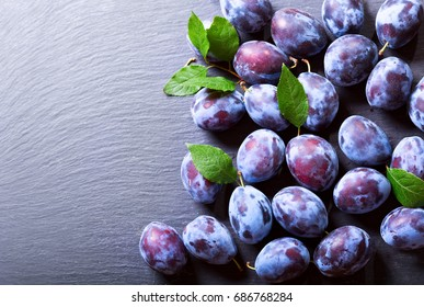 fresh blue plums on dark table, top view