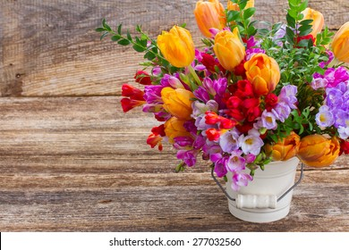 fresh blue, violet  and red freesia and orange tulip flowers  on wooden background