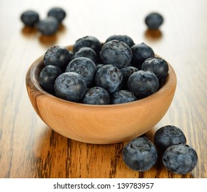 Fresh blueberries in a bowl on a brown table