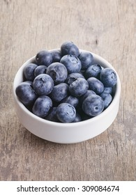 fresh blueberries in bowl on wood table, vintage toned