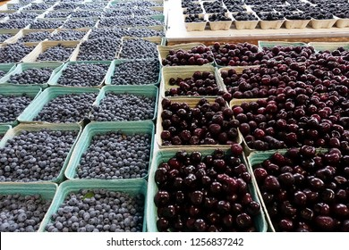 Fresh blueberries and cherries fully contain in each paper box in fruit market.