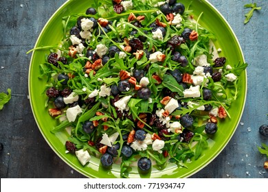 Fresh Blueberries, Cranberry salad with arugula, nuts, feta cheese, olive oil, herbs. Morning, breakfast healthy food.