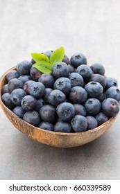 Fresh blueberries natural coconut in a bowl on a gray background.