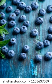 Fresh blueberries on blue rustic wooden table pattern. Healthy organic seasonal fruit background design. Organic food blueberries and mint leaf for healthy lifestyle.