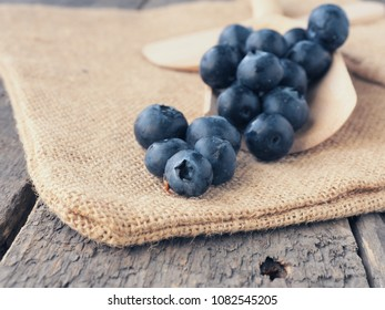 Fresh blueberries on a wooden spoon, healthy eating or food background