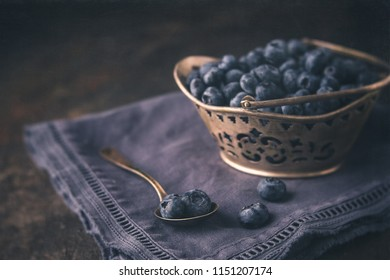 Fresh Blueberries in a Silver Basket; Some Isolated in Silver Spoon; Dark Blue Napkin on Black Background; Low Key Image