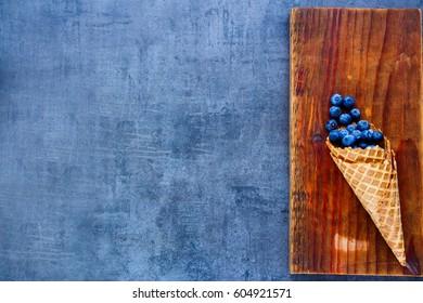 Fresh blueberries in waffle cones on vintage wooden board over dark background, top view, copy space. Fresh healthy raw vegan summer dessert concept