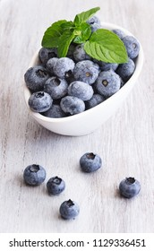 Fresh blueberries in a white bowl, with meant leaves on a wooden background