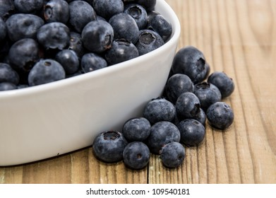 Fresh Blueberries in a white bowl on wooden background