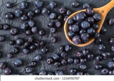 Fresh blueberries in a wooden spoon on dark stone table. Concept of healthy and dieting eating. Ripe and juicy fresh picked berries. Top view