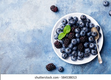 Fresh blueberry and blackberry berries with mint leaves on a white plate on blue stone background. Top view. Copy space.