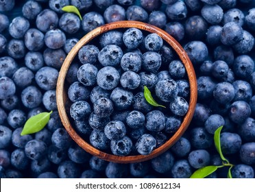 Fresh blueberry with drops of water in wooden bowl. Top view. Concept of healthy and dieting eating