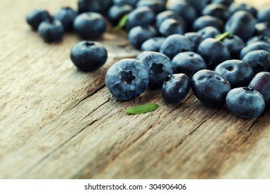 Fresh blueberry, great bilberry or bog whortleberry on wooden rustic board