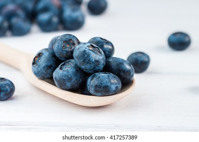 Fresh blueberry on wooden spoon. Creative blueberry on wooden white background. Close-up
