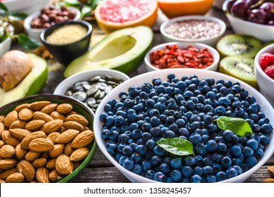 Fresh blueberry and other healthy food on table. Breakfast in a bowls with superfood, organic diet with fruits, nuts and berries.