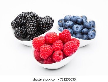 Fresh blueberry raspberry and blackberry in white bowl closeup on white background